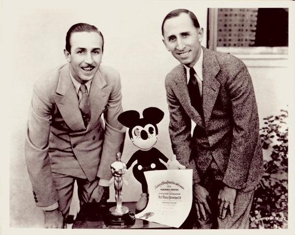 Una foto histórica que muestra a los hermanos Disney junto a un muñeco de Mickey y un premio Oscar
