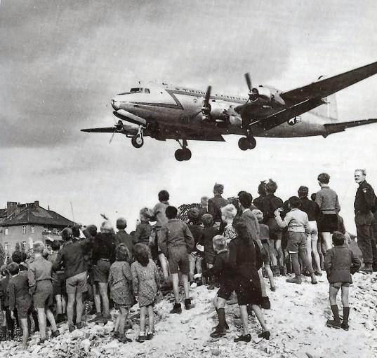 Fotografía que muestra a la gente esperando los suministros que llegaban por avión
