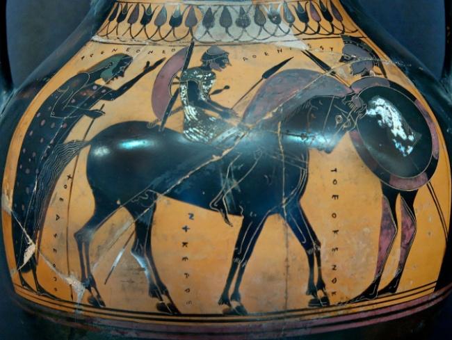 Pieza cerámica de figuras negras en las que se representa un hippeus(singular de hippeis con su caballo y su equipamiento militar para la caballería.
